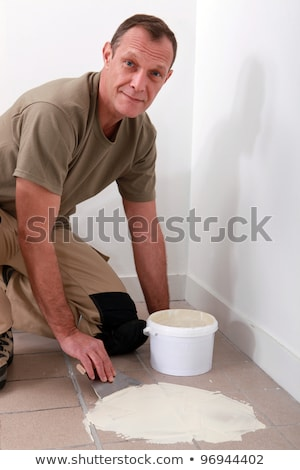 Handyman spreading adhesive over an old tiled floor Stock photo © photography33