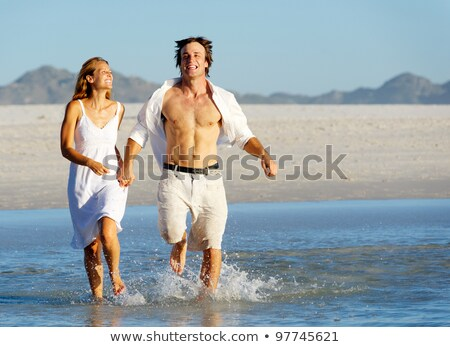 Playful young couple running through water Stock photo © photography33