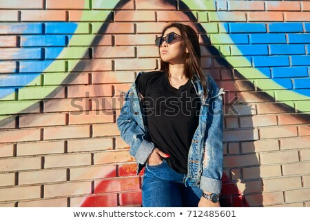Woman against grafitti wall  Stock photo © Fernando_Cortes