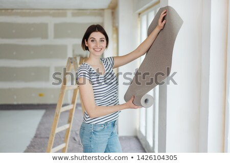 Woman hanging wallpaper in new house Stock photo © photography33
