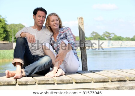 couple sat on jetty stock photo © photography33
