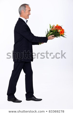 Man dressed in tuxedo holding bunch of lowers Stock photo © photography33