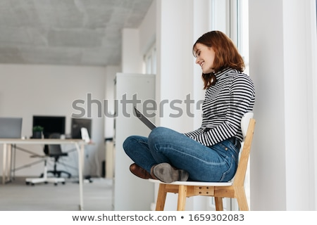 Woman sitting cross-legged with her laptop Stock photo © photography33