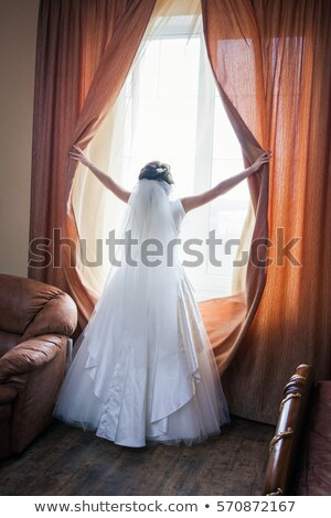 portrait of young girl behind white curtain looking towards the  Stock photo © carlodapino