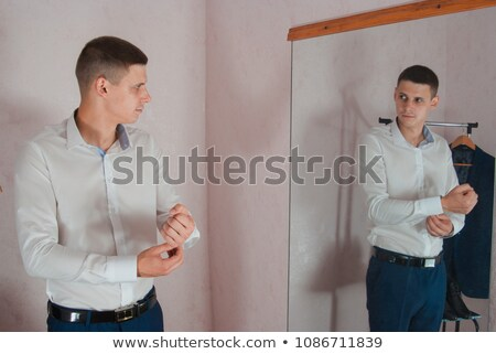 young man posing near the mirror stock photo © deandrobot