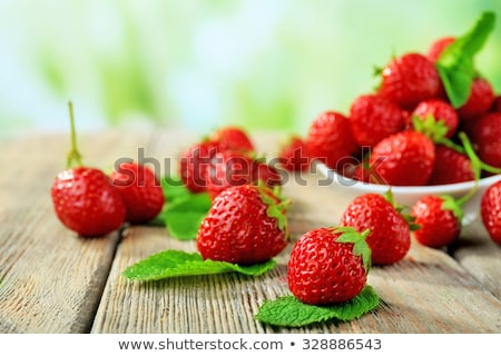 Ripe strawberries in saucer on wooden table on natural green blu Stock photo © Yatsenko