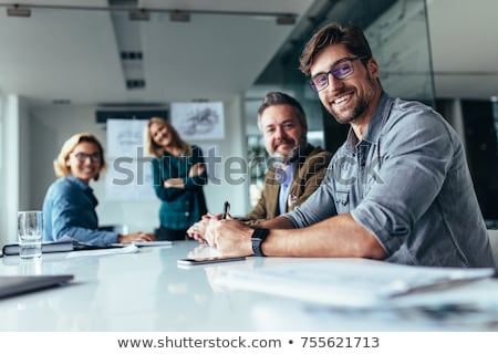 business people sitting at tables in an office stock photo © vectorikart