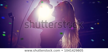 cheerful female singer performing in illuminated nightclub stock photo © wavebreak_media