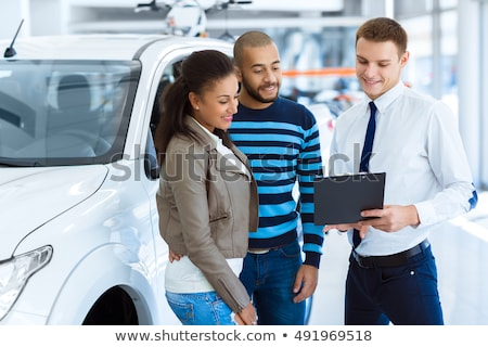 handsome salesman filing documents with his happy clients stock photo © deandrobot