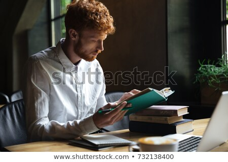 photo of serious readhead bearded student preparing for exam in stock photo © deandrobot