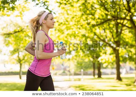 Young blonde sports woman in park holding bottle with water showing okay gesture. Stock photo © deandrobot