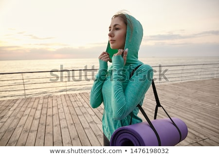 Woman make stretching exercises outdoors. Stock photo © deandrobot