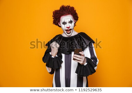 Happy clown using smartphone and making winner gesture Stock photo © deandrobot
