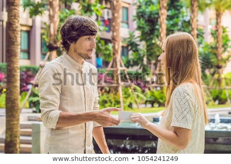 a woman gives to a man security key card or business card stock photo © galitskaya