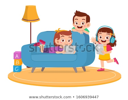 Stockfoto: Boy uses a tablet at home on the couch in the background of a window with skyscrapers. Modern childr