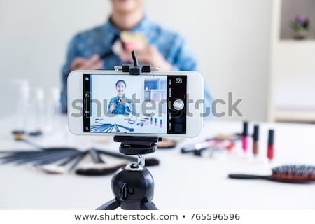 Happy smiling elegant woman or beauty blogger with brush on reco Stock photo © Freedomz