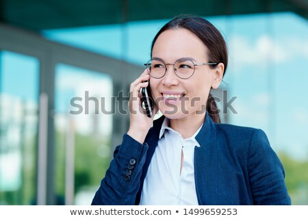 Young smiling brunette businesswoman discussing working moments on smartphone Stock photo © pressmaster