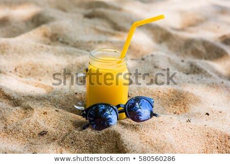 Кубок апельсиновый сок соломы песчаный пляж напитки отпуск Сток-фото © dolgachov