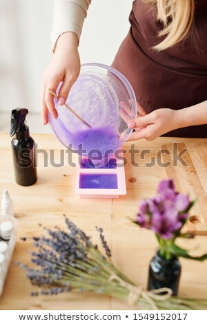 Young woman pouring lavender scented liquid soap mass into silicone molds Stock photo © pressmaster