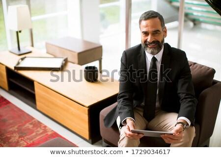 Elegant mature business man using multitasking multimedia digita Stock photo © boggy