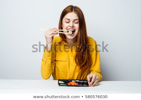 Stock photo: beautiful woman eating sushi with chopsticks