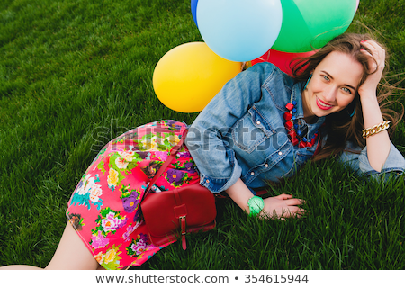 Portrait of a pretty cool girl lying on the grass  stock photo © OleksandrO