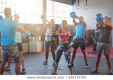 Kettlebells swing crossfit exercise man and woman Stock photo © lunamarina
