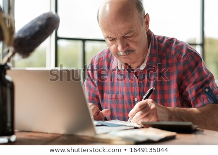 mature man taking notes from work at his home stock photo © tab62