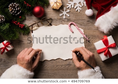 close up of christmas wishlist letter in santa claus hands stock photo © hasloo