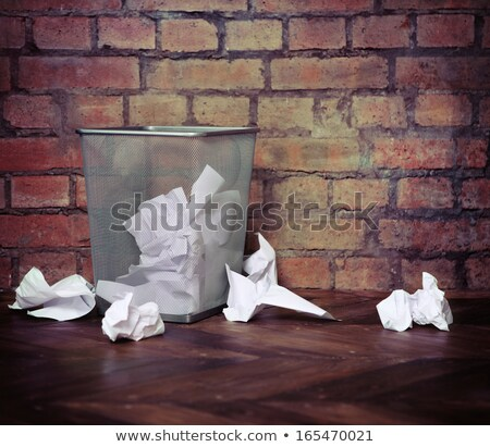 Recycle bin filled with crumpled papers. Brick wall background Stock photo © dashapetrenko