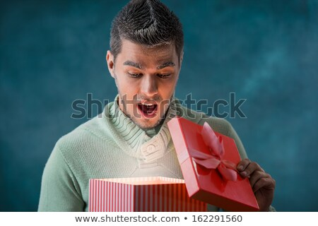 happy young man opening a gift box outdoors at night on christma stock photo © hasloo