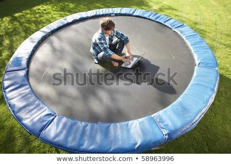 Jonge man ontspannen trampoline laptop computer man Stockfoto © monkey_business