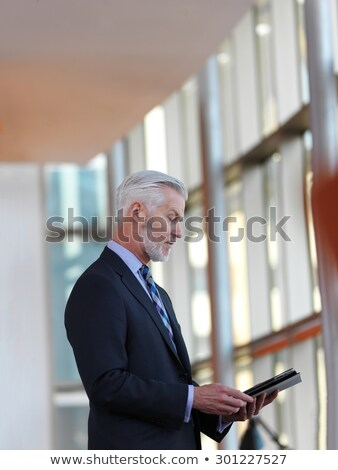 fashion man holding and looking at a tablet pad computer. stock photo © feedough