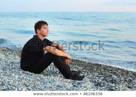 sitting teenager boy on stone seacoast, Looking afar Stock photo © Paha_L