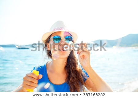Youngwoman blowing soap bubbles on the seashore Stock photo © vlad_star