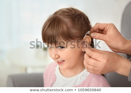 doctor putting hearing aid in patients ear stock photo © andreypopov