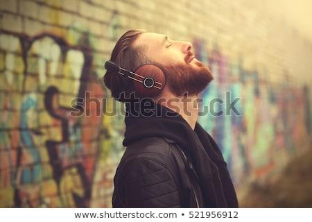 счастливым · молодые · черным · человеком · наушники · смартфон - Сток-фото © rastudio