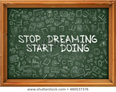 Hand Drawn Stop Dreaming Start Doing on Green Chalkboard. Stock photo © tashatuvango