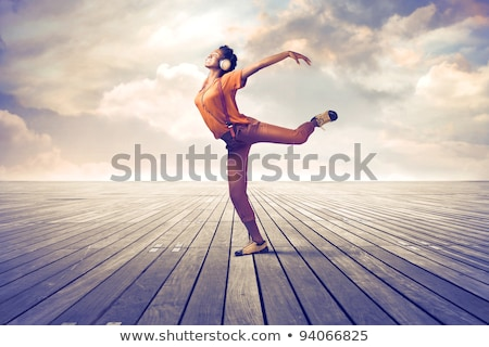 young sports woman posing outdoors listening music dancing stock photo © deandrobot