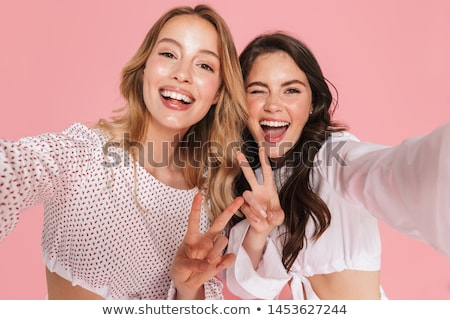 cute young woman posing isolated over pink background make peace gesture stock photo © deandrobot