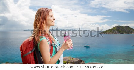 Stock photo: happy woman with backpack over seychelles island