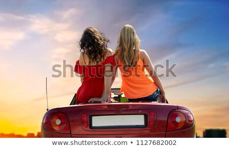 Stock photo: women sitting on convertible car over city sunset