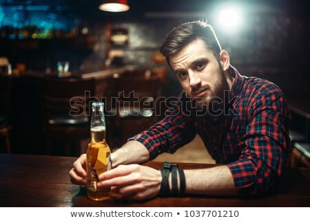 Stock photo: drunk man with beer bottles on table at night
