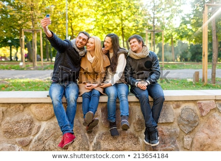friends taking selfie by smartphone in autumn park stock photo © dolgachov