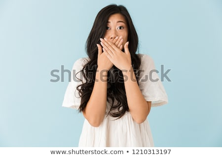 Shocked scared young asian beautiful woman posing isolated over blue background. Stock photo © deandrobot