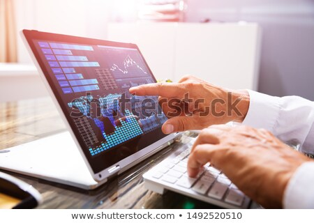 Businessman Analyzing Graph On Convertible Laptop Stock photo © AndreyPopov
