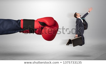 Stok fotoğraf: Giant Hand Gives A Kick To A Small Businessman