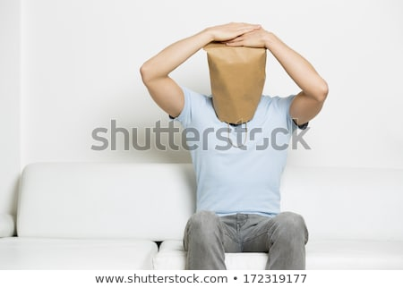 Miserable anonymous man with head covered sitting on sofa. Stock photo © lichtmeister