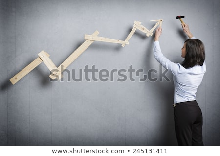 confident woman building positive trend graph with hammer in han stock photo © lichtmeister
