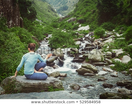 Woman doing Ashtanga Vinyasa Yoga asana outdoors at waterfall Stock photo © dmitry_rukhlenko